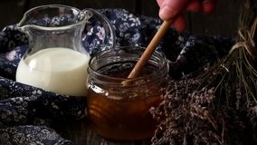 Abra el tarro de cristal de miel líquida con el panal y metrajes
