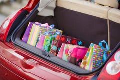 Abra el tronco del coche con los bolsos de compras Imagen de archivo libre de regalías