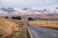 Abra a estrada do alcatrão dirigida no horizonte nas terras Foto de Stock Royalty Free