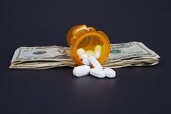 Abra a garrafa de comprimido da prescrição em uma pilha de dinheiro Imagem de Stock Royalty Free
