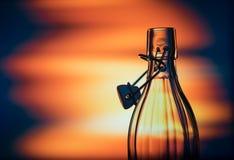 Abra a garrafa de vidro na frente de um fundo criativo Fotos de Stock Royalty Free