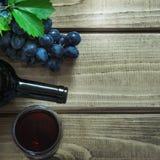 Abra a garrafa do vinho tinto com um vidro, um corkscrew e uma uva madura em uma placa de madeira Copie o espaço e a vista superi Fotos de Stock Royalty Free