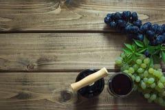 Abra a garrafa do vinho tinto com um vidro, um corkscrew e uma uva madura em uma placa de madeira Copie o espaço e a vista superi Imagem de Stock Royalty Free