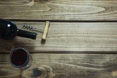 Abra a garrafa do vinho tinto com um vidro, corkscrew em uma placa de madeira Copie o espaço e a vista superior Fotos de Stock