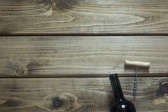 Abra a garrafa do vinho tinto, corkscrew em uma placa de madeira Copie o espaço e a vista superior Fotos de Stock Royalty Free