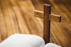 Abra la biblia con el icono del crucifijo detrás Imagen de archivo