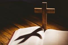 Abra la biblia con el icono del crucifijo detrás Imágenes de archivo libres de regalías