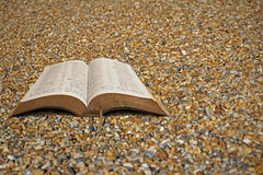 Abra la biblia en los guijarros de la playa Imagen de archivo libre de regalías