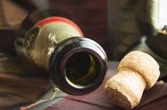 Abra la botella de champán y el corcho en la tabla con un mantel Imagen de archivo libre de regalías