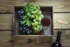 Abra la botella de vino con un vidrio, un sacacorchos y una uva madura en bandeja en un fondo de madera Fotos de archivo