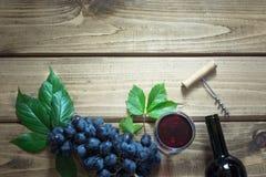 Abra la botella de vino rojo con un vidrio, un sacacorchos y una uva madura en un tablero de madera Copie el espacio y la visión  Imagenes de archivo