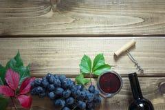 Abra la botella de vino rojo con un vidrio, un sacacorchos y una uva madura en un tablero de madera Copie el espacio y la visión  Fotografía de archivo libre de regalías