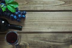 Abra la botella de vino rojo con un vidrio, un sacacorchos y una uva madura en un tablero de madera Copie el espacio y la visión  Fotografía de archivo