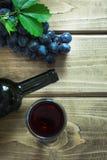 Abra la botella de vino rojo con un vidrio, un sacacorchos y una uva madura en un tablero de madera Copie el espacio y la visión  Imagen de archivo libre de regalías