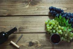 Abra la botella de vino rojo con un vidrio, un sacacorchos y una uva madura en un tablero de madera Copie el espacio y la visión  Fotos de archivo