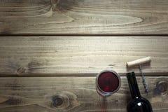 Abra la botella del vino rojo con un vidrio, sacacorchos en un fondo de madera Copie el espacio Imagenes de archivo