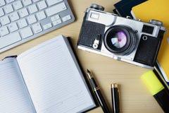 Abra la cámara del cuaderno de notas, del teclado y del vintage en un DES de madera Foto de archivo