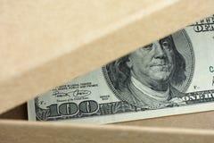 Abra la caja con cientos dólares de billete de banco en ella Imágenes de archivo libres de regalías