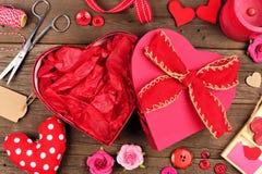 Abra la caja de regalo en forma de corazón del día de tarjetas del día de San Valentín con el marco contra la madera fotografía de archivo