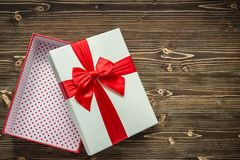 Abra la caja del Año Nuevo o de regalo de la Navidad con la cinta roja para el día de fiesta Fotografía de archivo