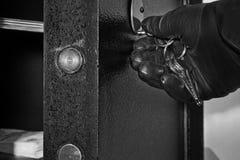Abra la caja fuerte con la mano del ladrón fotos de archivo