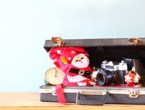 Abra la cartera con las decoraciones de la Navidad y la cámara delante de la opinión de la playa Concepto del día de fiesta de la Imágenes de archivo libres de regalías
