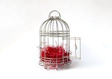 Abra la jaula de pájaros de acero con los pedazos de papel rojo como jerarquía aislada en el fondo blanco Fotografía de archivo