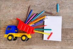 Abra la libreta blanca con los rotuladores y las plumas de bola coloridos en la tabla de madera Fotografía de archivo