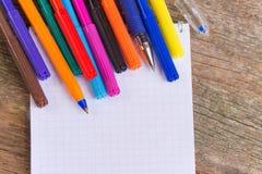 Abra la libreta blanca con los rotuladores y las plumas de bola coloridos en la tabla de madera Fotografía de archivo libre de regalías