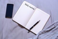 Abra la libreta con la pluma negra con la inscripción y el lugar para las mentiras del texto en la cama con un smartphone El conc imagen de archivo