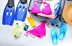 Abra la maleta con los accesorios personales de la materia y de la playa en fondo ligero Fotos de archivo