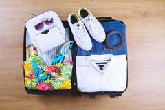 Abra la maleta con ropa femenina casual en la opinión superior del piso de madera Concepto del bolso del viaje Fotografía de archivo libre de regalías