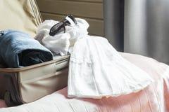 Abra la maleta con ropa femenina en la cama Fotos de archivo