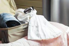 Abra la maleta con ropa femenina en la cama Foto de archivo libre de regalías