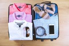 Abra la maleta con ropa y accesorios femeninos de moda en la opinión superior del piso de madera, espacio de la copia, imagen ent Fotos de archivo libres de regalías