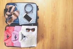 Abra la maleta con ropa y accesorios femeninos de moda en la opinión superior del piso de madera, espacio de la copia, imagen ent foto de archivo libre de regalías