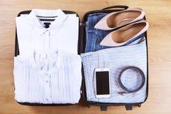 Abra la maleta con ropa y accesorios femeninos de moda en la opinión superior del piso de madera, espacio de la copia, imagen ent Fotos de archivo