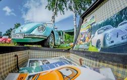 Abra la maleta elegante del vintage con las revistas sobre Volkswagen Beetle y el transportador Foto de archivo