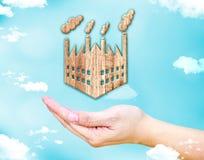 Abra la mano femenina con el icono de madera de la fábrica con el cielo azul y la nube, Imagenes de archivo