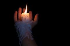 Abra la mano que sostiene el palillo de la vela con la cera que fluye abajo del brazo Fotos de archivo libres de regalías