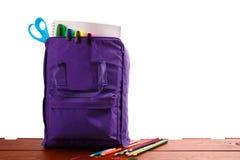 Abra la mochila púrpura con las fuentes de escuela en la tabla de madera De nuevo a Cierre para arriba Fotos de archivo