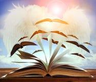Abra la página del libro viejo en la tabla de madera con la página del libro de vuelo contra b Fotografía de archivo
