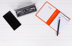 Abra la página en blanco del organizador personal con una pluma, vidrios en ope Foto de archivo