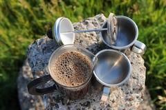 Abra la prensa del francés con café recientemente preparado de la espuma y dos tazas en un soporte de piedra en el aire abierto Fotos de archivo libres de regalías