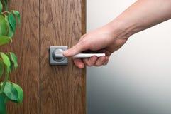 Abra la puerta Cerca - para arriba de la mano masculina en el tirador de puerta de acero tex foto de archivo