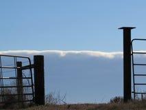 Abra la puerta de la granja en el frente del cielo azul y de la nube Imagenes de archivo