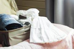 Abra la puerta de madera y véala al dormitorio Abra la maleta con ropa femenina en la cama Imagenes de archivo