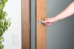 Abra la puerta La mano de un hombre en el tirador de puerta Madera y luz oscuras fotos de archivo libres de regalías