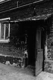 Abra la puerta vieja que lleva en una entrada oscura Foto de archivo libre de regalías