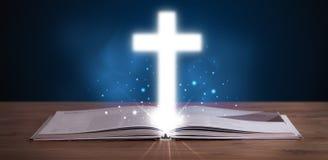 Abra la Sagrada Biblia con brillar intensamente cruzado en el centro Fotografía de archivo libre de regalías